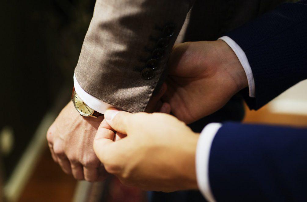 Cropped hands of sales clerk adjusting customer's sleeve in clothing store